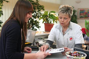 Foto: Frau wird von einer DRK-Mitarbeiterin bei der Blutspende  empfangen.